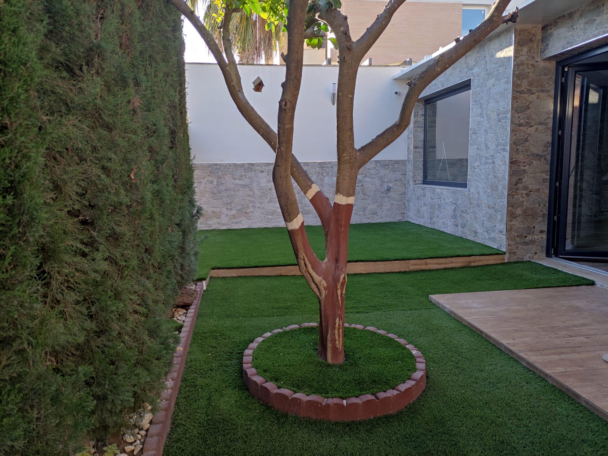 terraza con césped sintético y árboles