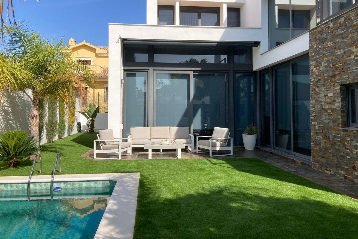 vivienda con césped artificial y piscina